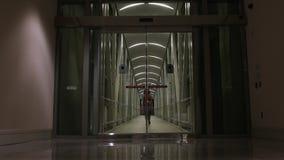 A mulher anda para a porta de vidro de deslizamento vídeos de arquivo