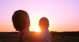 Mulher animador com uma criança nas mãos que olham o ar livre esplêndido do por do sol no slo-mo filme