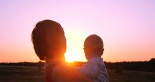 Mulher animador com uma criança nas mãos que olham o por do sol esplêndido fora fotografia de stock