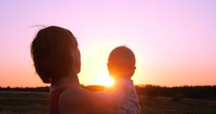 Mulher animador com uma criança nas mãos que olham o por do sol esplêndido fora fotos de stock