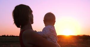 Mulher animador com uma criança nas mãos que olham o por do sol esplêndido fora foto de stock