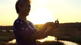 A mulher animador gerencie um girador em um banco do lago no verão no slo-mo filme