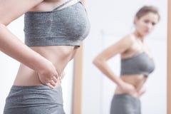 Mulher anoréxico que olha-se em um espelho imagem de stock
