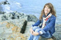 A mulher 60 anos de vista para o mar velha senta-se Foto de Stock Royalty Free