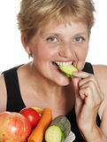 Mulher (67 anos velho) que come vegetais Foto de Stock Royalty Free