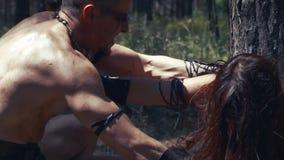 A mulher antiga na roupa de couro luta um homem bárbaro, na floresta filme