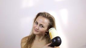 A mulher após ter tomado um chuveiro seca o cabelo molhado vídeos de arquivo