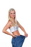 Mulher após uma dieta bem sucedida com grandes calças Fotografia de Stock Royalty Free