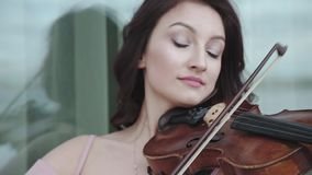 Mulher apaixonado que joga entusiasticamente no violino na construção video estoque