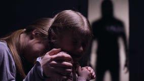 Mulher apavorado e criança que olham a silhueta assustador do monstro fora da porta video estoque