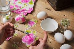 A mulher aplica a colagem no ovo da páscoa colorido, técnica do decoup Fotos de Stock Royalty Free
