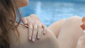 A mulher aplica com cuidado a loção hidratando no corpo que tem o resto perto da piscina video estoque