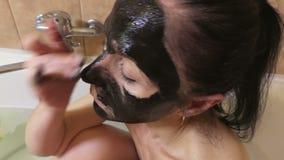 A mulher aplica a máscara de creme preta da limpeza vídeos de arquivo