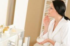 A mulher aplica o creme de face que olha o espelho do banheiro Imagem de Stock