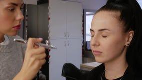 A mulher aplica o ocultador do aerógrafo video estoque