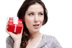 A mulher aplica sua orelha ao presente Fotos de Stock Royalty Free