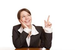 A mulher aponta e olha acima no espaço em branco do anúncio fotografia de stock royalty free