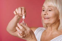 Mulher aposentada índice que usa o verniz de prego Imagens de Stock