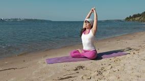 Mulher aposentada idosa que faz alguma ioga na praia video estoque