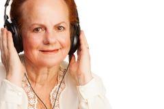 Mulher aposentada positiva que escuta a música Imagem de Stock