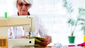 Mulher aposentada que usa a máquina de costura video estoque