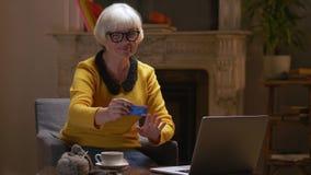 Mulher aposentada que usa o cartão de crédito para pagar em linha das compras ao domicílio filme