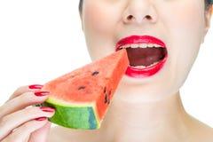 A mulher aprecia comer a melancia com bordos vermelhos, mordida, verniz para as unhas Fotos de Stock Royalty Free
