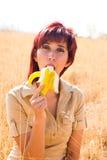 A mulher aprecia comer uma banana Imagens de Stock