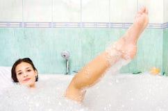 A mulher aprecia a espuma do banho na banheira Imagens de Stock Royalty Free