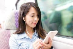 A mulher aprecia a música no compartimento do trem do interior do telefone celular imagem de stock