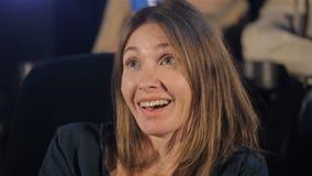 A mulher aprecia olhar o filme no cinema video estoque