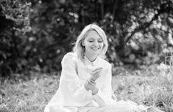 A mulher aprecia para relaxar o fundo da natureza A senhora aprecia a fragr?ncia da flor da proposta Femininity e ternura Louro m imagem de stock