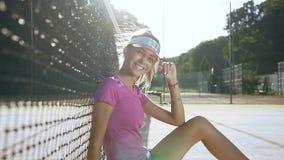 Mulher apta atrativa que sorri na câmera ao sentar-se em um campo de tênis perto da rede video estoque