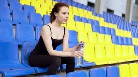 A mulher apta bebe a água em uma tribuna do estádio vídeos de arquivo