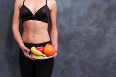 Mulher apta com uma placa dos frutos, espaço da cópia Dieta, cuidados médicos, fotos de stock