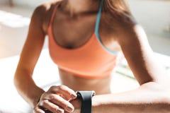 A mulher apta da foto após a sessão do exercício verifica resultados no smartwatch na aptidão app Fotografia de Stock Royalty Free