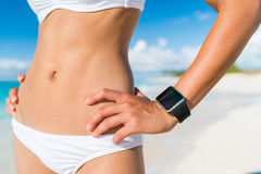 Mulher apta do biquini que veste o smartwatch wearable da tecnologia fotografia de stock