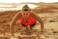 A mulher apta dos jovens nos esportes alinha no litoral que faz flexões de braço fotografia de stock