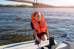 Mulher apta dos jovens pronta para montar os esquis de água que situam no close up do barco Esqui aquático do atleta e divertimen Fotos de Stock