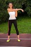 Mulher apta dos jovens que estica na máscara exterior na tarde do verão Imagens de Stock Royalty Free
