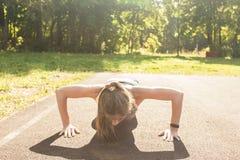 Mulher apta dos jovens que exercita fazendo impulso-UPS fora Imagens de Stock Royalty Free