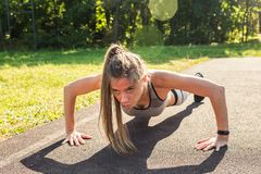 Mulher apta dos jovens que exercita fazendo impulso-UPS fora Imagem de Stock Royalty Free