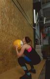 Mulher apta dos jovens que exercita jogando uma bola acima em um gym Imagens de Stock