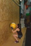 Mulher apta dos jovens que exercita jogando uma bola acima em um gym Fotografia de Stock