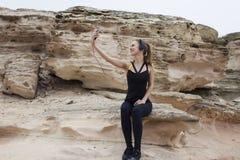 Mulher apta dos jovens que usa o telefone celular ao falar com seu amigo sobre a vida ativa do esporte e a natureza bonita ao red Imagens de Stock