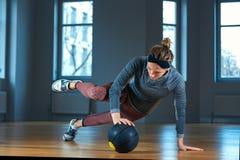 Mulher apta e muscular que faz o exercício intenso do núcleo com kettlebell no gym Exercício fêmea no gym do crossfit imagem de stock
