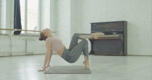 Mulher apta flexível que faz esticando o exercício video estoque