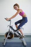 Mulher apta na bicicleta da rotação que sorri na câmera foto de stock