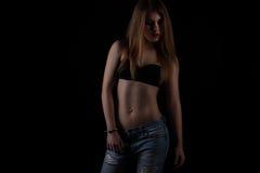 Mulher apta nas calças de brim, fundo preto dos jovens Fotografia de Stock