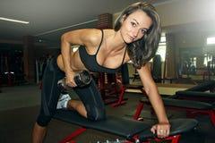 Mulher apta no gym que faz uma fileira de um braço imagem de stock royalty free